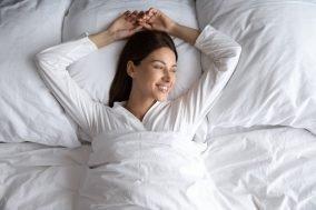 zadovoljna zena lezi u krevetu