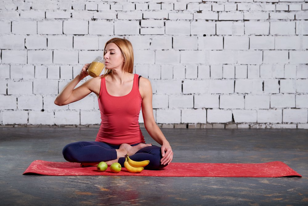 devojka ispija smoothie dok radi jogu