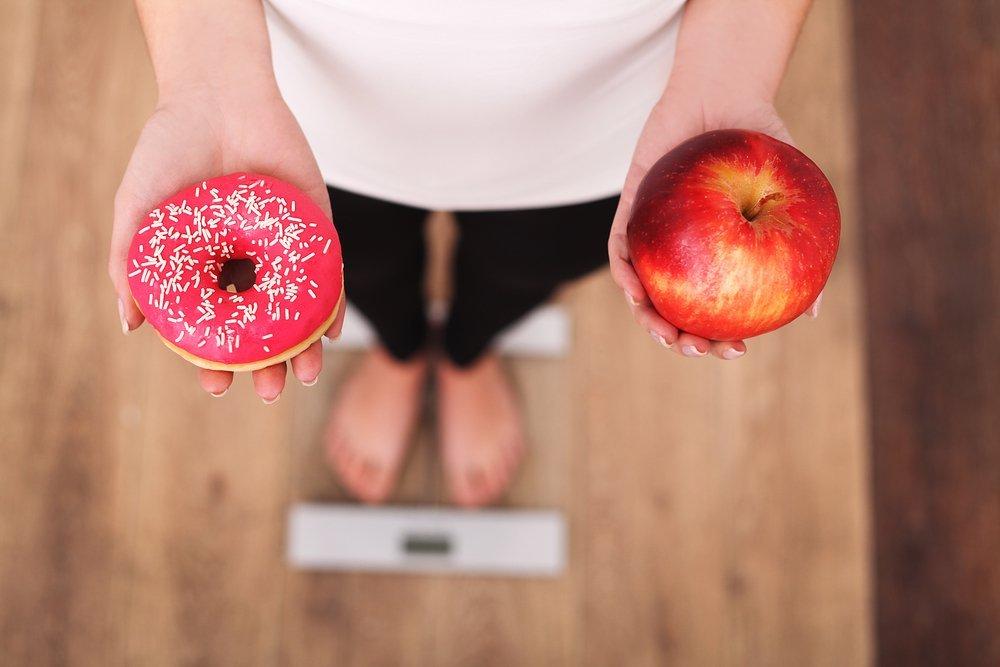 krofna ili jabuka - zena stoji na vagi za merenje