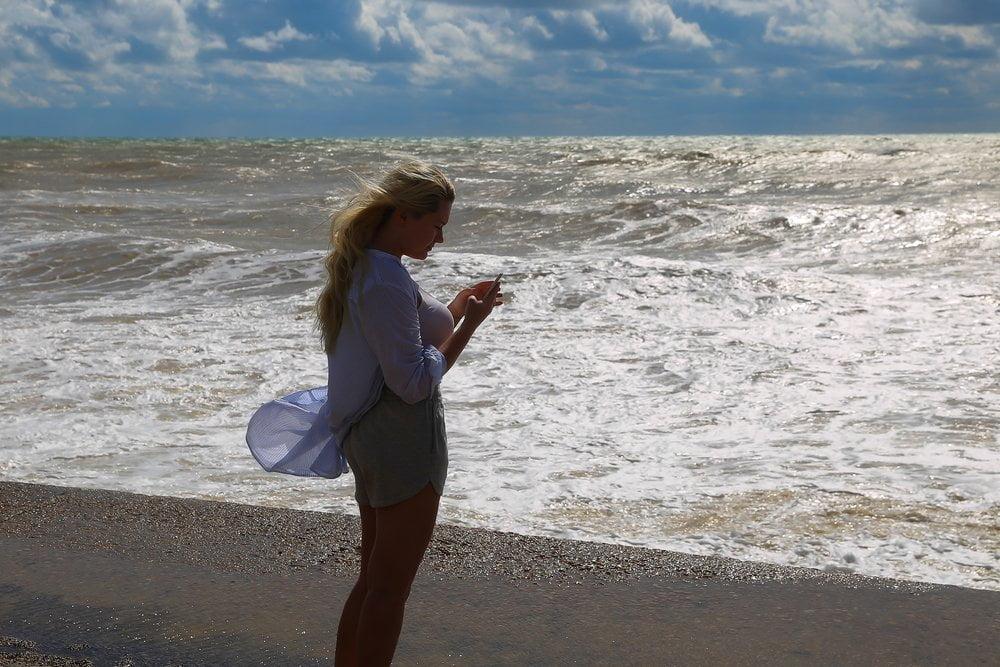 devojka na plazi cita sa telefona