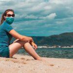 zena sedi u pesku na plazi sa zastitnom maskom