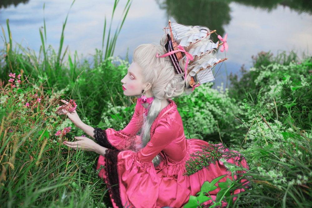 devojka kraj jezera sa belom baroknom perikom