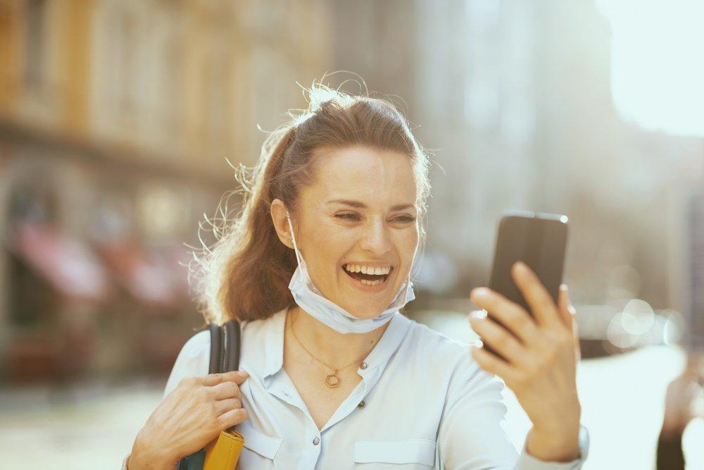 zena se smeje dok gleda u telefon