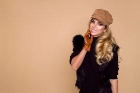 nasminkana zena sa kapom i rukavicama