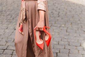 zena nosi crvene cipele u ruci