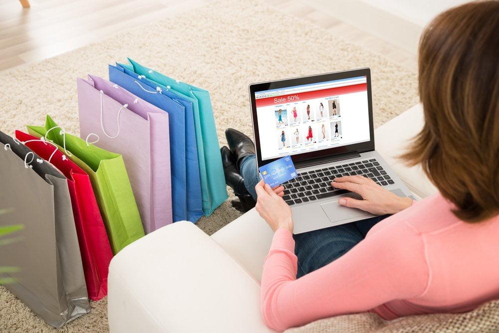 online soping, devojka drzi karticu na racunaru