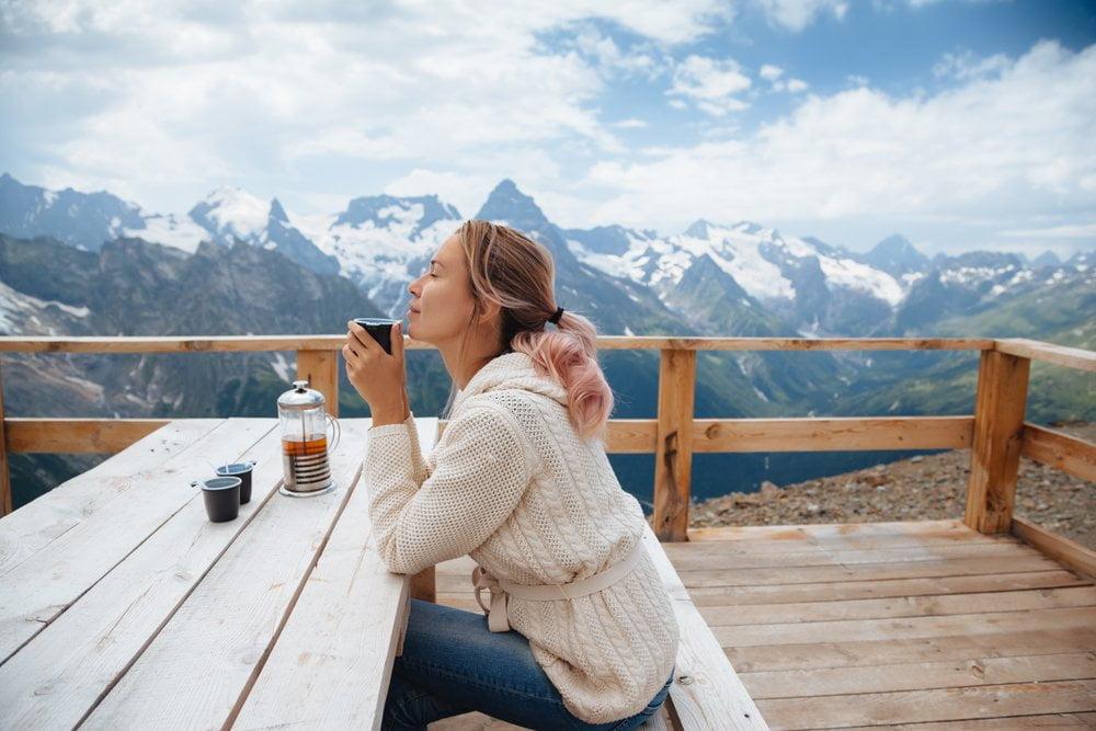 devojka ispija caj na planini