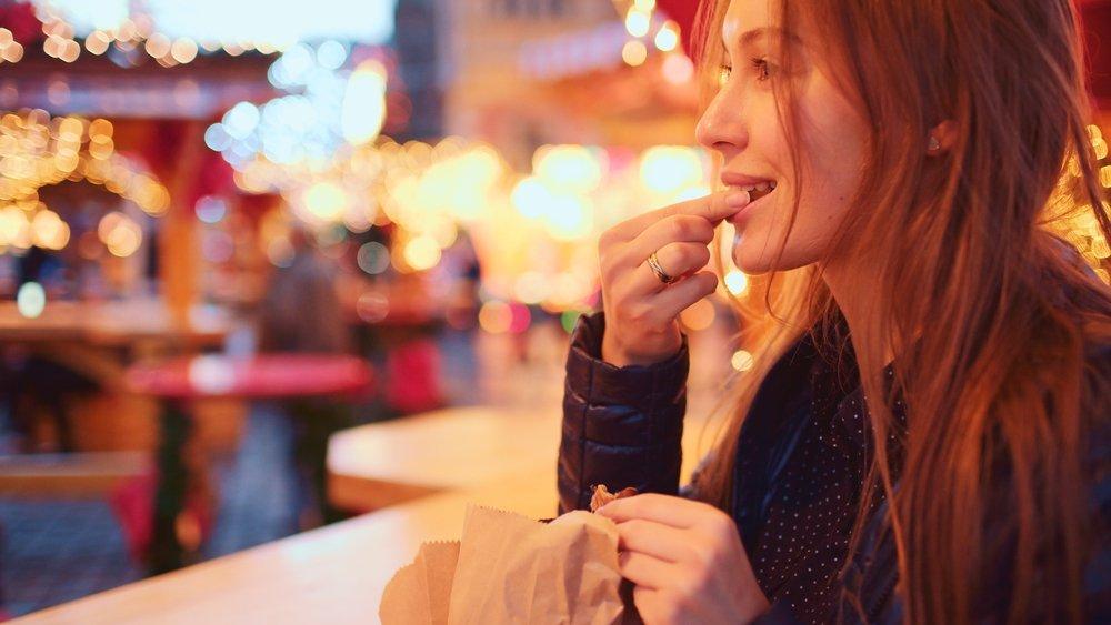 devojka jede kestenje na ulici