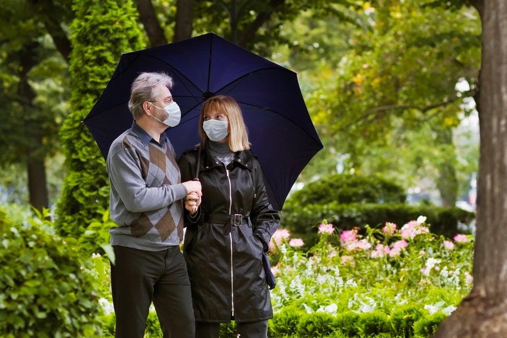 stariji par seta po parku sa maskama
