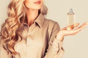 žena drži bocu parfema