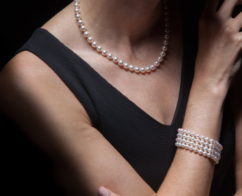 žena sa bisernom ogrlicom i narukvicom