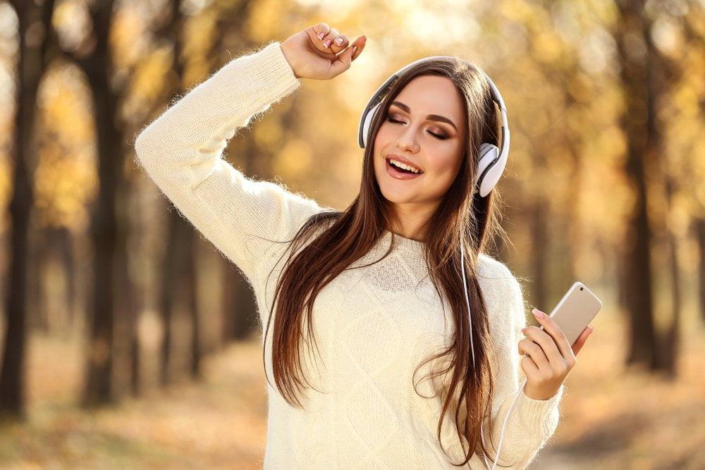 devojka sa slušalicama šeta po šumi
