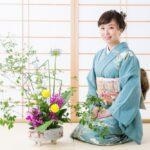 Žena u kimonu sedi pored cveća