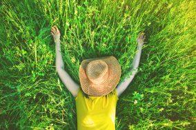 devojka u travi sa šeširom na glavi
