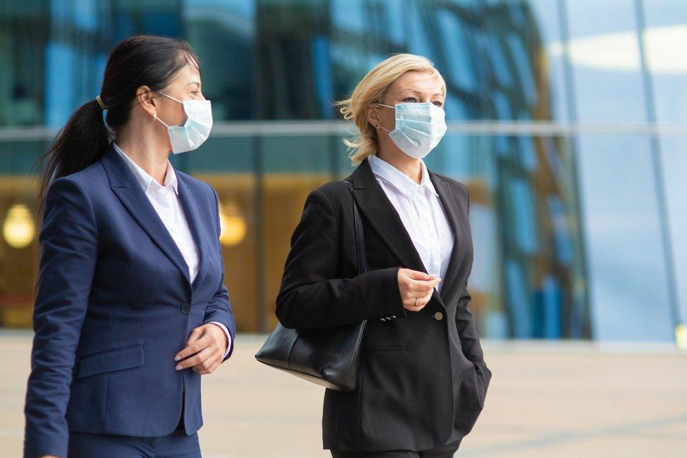 dve poslovne žene se šetaju sa maskama