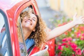 nasmejana devojka u crvenim kolima