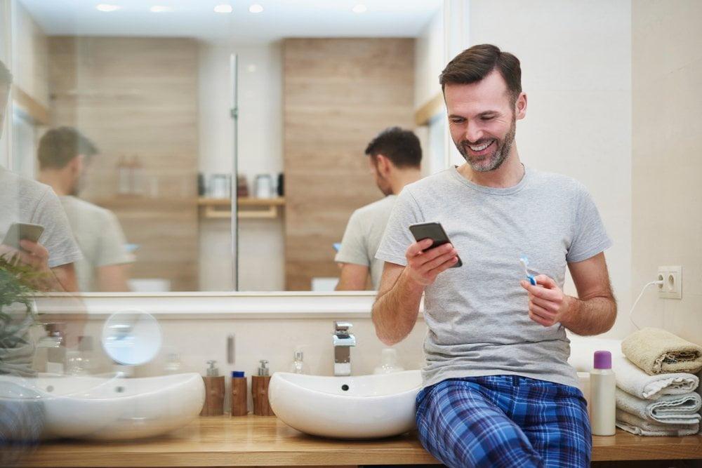 covek gleda u telefon u kupatilu