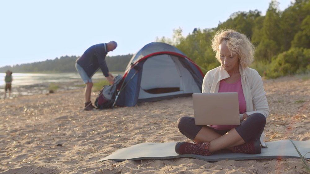 zena radi na laptopu na plazi