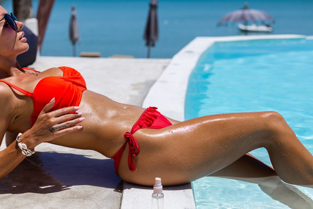 preplanula devojka se sunca na bazenu
