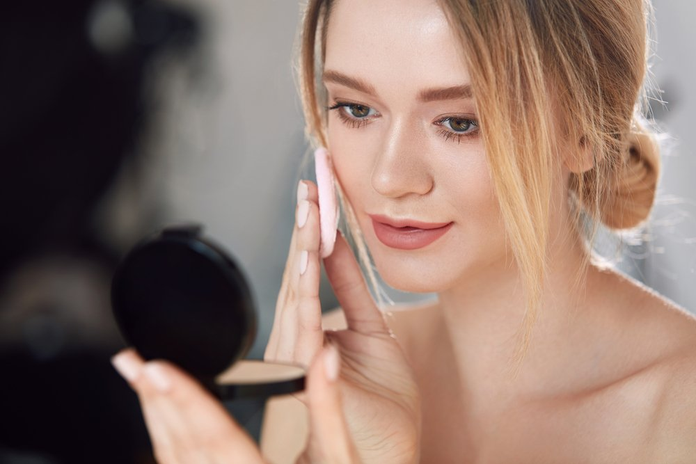 girl is putting on a make-up