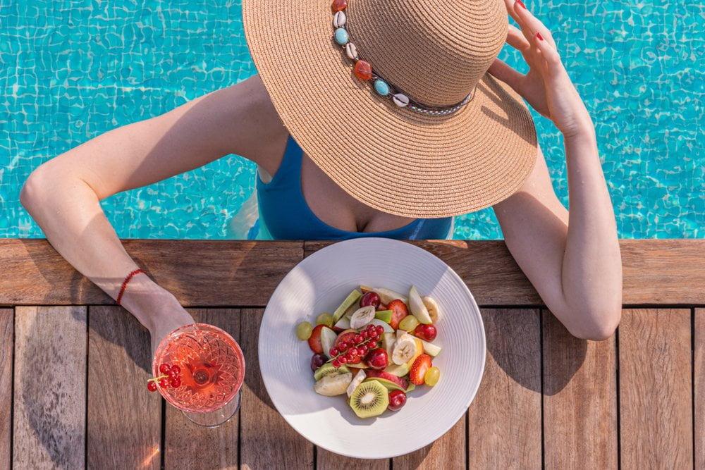 Žena na bazenu i tanjir voća