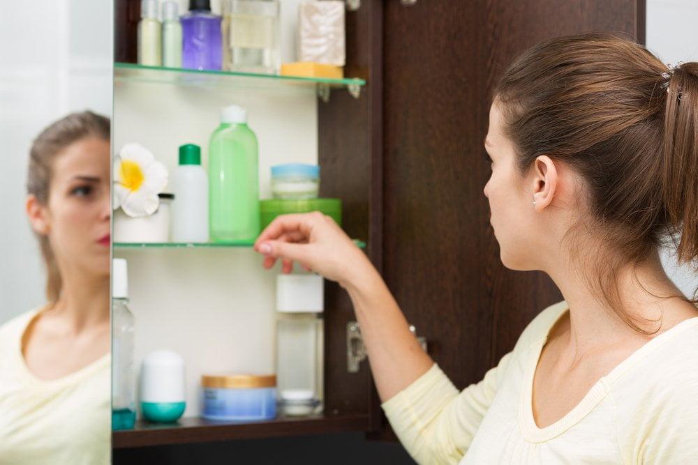 Žena i kozmetički proizvodi u kupatilu
