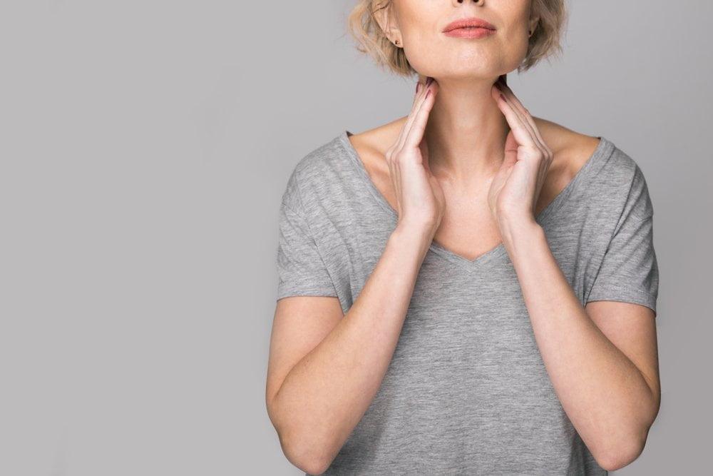 Žena opipava vrat u predelu tiroidne žlezde