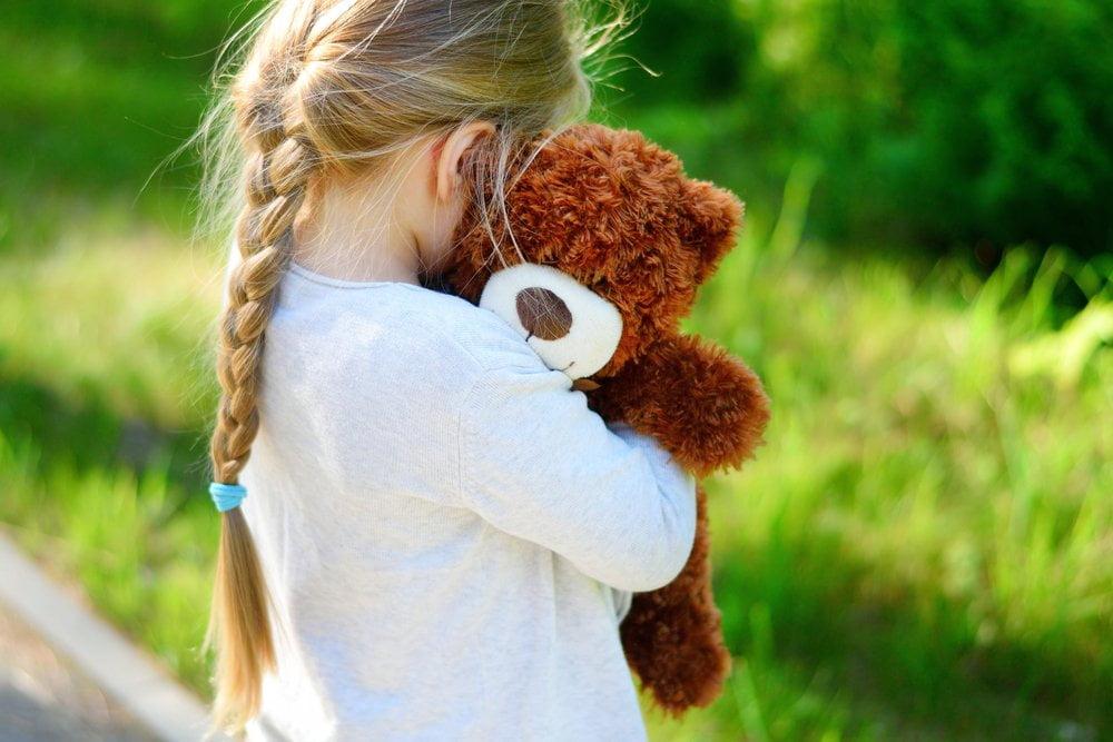 Devojčica sa plišanim medom u rukama