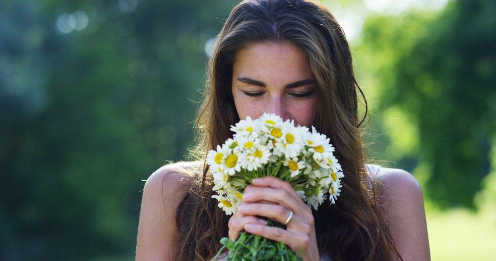 Žena koja miriše buket cveća